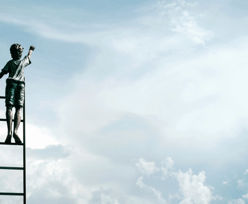 Boy on ladder painting in sky